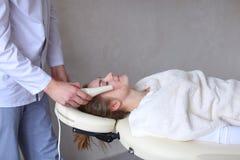 美容师人做特别面孔按摩给有cosmet的女孩 库存照片