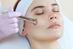 美容师做做法Microdermabrasion一个美丽,少妇的面部皮肤美容院的 免版税库存照片