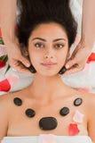 美容师做妇女的石按摩温泉在健康中心 免版税库存照片