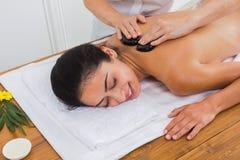 美容师做妇女的石按摩温泉在健康中心 图库摄影