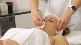 美容师做着面孔削皮面具,温泉女孩的秀丽治疗 股票录像