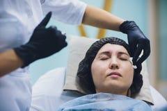 美容师医生做面部秀丽射入给她的妇女客户 美好的女性面孔和美容师的手 库存照片