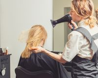 美容师吹干妇女在美容院的` s头发 免版税库存照片