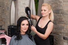 美容师吹干的妇女头发在给在客厅的新的理发以后 免版税库存照片