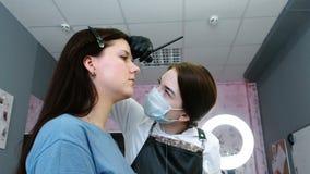 美容师在有刷子的客户` s眼眉上把油漆放 侧视图 眼眉更正 股票录像