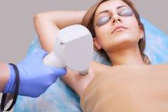 美容师在腋窝区域做激光头发移动程序, 免版税库存照片