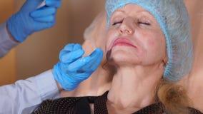 美容师在面孔的干净的皮肤上把一支麻醉的软膏放 影视素材