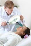 美容师审查的患者的皮肤状况 库存图片