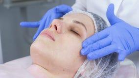 美容师应用一种起泡沫的清洁剂于年轻女人的客户的面孔 面孔和手特写镜头 股票录像