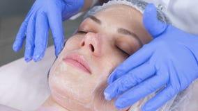 美容师应用一种起泡沫的清洁剂于年轻女人的客户的面孔 面孔和手特写镜头 影视素材