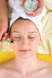 美容师应用在妇女眼睛的奶油 免版税库存图片