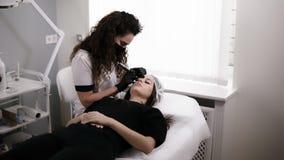 美容师得出形状或做更正有针的眼眉发廊的一名妇女的 ?? 影视素材