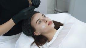 美容师手的关闭在耐心面孔上把奶油放在治疗,慢动作以后 影视素材