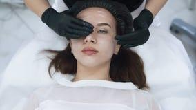 美容师手的关闭应用在耐心面孔的奶油,按摩它,慢动作 股票视频
