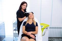 美容师执行在患者的面孔的做法与与氢结合削皮用具 洗涤和回复 免版税库存图片
