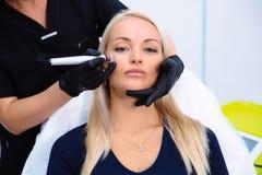美容师执行在患者的面孔的做法与与氢结合削皮用具 洗涤和回复 免版税库存照片