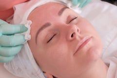 美容师抹湿抹妇女的面孔 洗涤和润湿皮肤 秀丽和健康在美容院里 免版税库存照片
