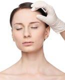 美容师接触和检查健康妇女表面。 免版税库存照片