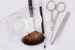 美容师有刷子、剪刀和镊子的工作地点 库存图片
