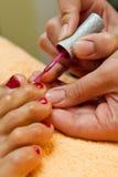 美容师照料给修脚化妆用品和绘红色钉子的女性客户的脚 免版税库存照片