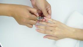 美容师用途飞剪机清洁和切开表皮在钉子和温泉沙龙 得到指甲盖修指甲服务的妇女 影视素材