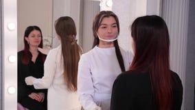 美容师看坐在镜子前面的一把椅子的女孩,专家估计患者 股票视频
