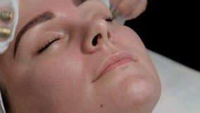 美容师磨擦鼻子,并且一名妇女的面颊在整容术办公室集中 一个美丽的女孩的面孔procedur的 影视素材
