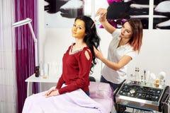 美容师给头发治疗有一个金面具的一个深色的客户在她的在现代美容院的面孔 图库摄影