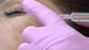 美容师进行在女孩的面颊的射入给患者 股票录像