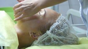 美容师递抚摸客户的面孔 面部按摩美丽的女孩 一个少妇的画象秀丽的 影视素材