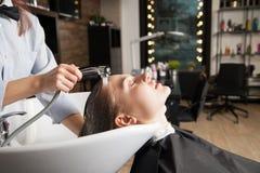 美容师洗涤的妇女` s头 免版税库存照片