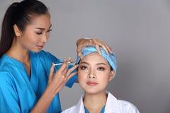 美容师Check Diagnose Face医生在p前的结构患者 免版税图库摄影