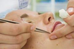 美容师depilating的镊子妇女 免版税库存图片