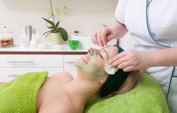 美容院。去除面部面具的化妆师从妇女面孔。 免版税库存图片