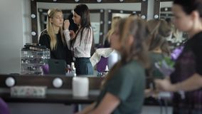 美容院的两个女朋友 女孩为党做准备 化妆师对构成做金发妇女 影视素材
