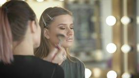 美容院的女孩 在构成的大师训练球的壮观的女孩 化妆师投入刷子 股票录像