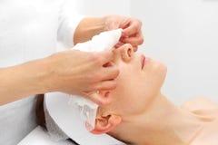 美容院的妇女在护肤治疗期间 免版税库存图片