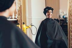 美容院的妇女看她的在镜子的反射 库存照片