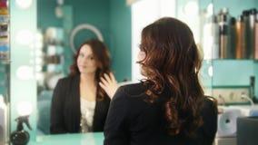 美容院的年轻浅黑肤色的男人敬佩她的在镜子的反射 影视素材