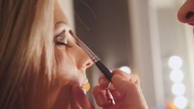 美容院:化妆师创造可爱的少妇,远距照相眼眉的构成  库存图片