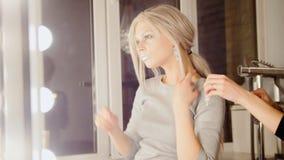 美容院:可爱的白肤金发的少妇模型穿戴耳环 库存照片