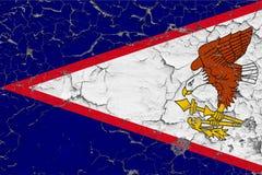 美属萨摩亚的旗子在破裂的肮脏的墙壁上绘了 葡萄酒样式表面上的全国样式 库存照片