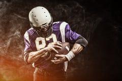 美式足球球员藏品球在他的在烟的手上 黑背景,拷贝空间 美国人的概念 库存照片