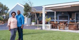 美满的非洲在他们的草坪的夫妇常设外部 免版税库存图片