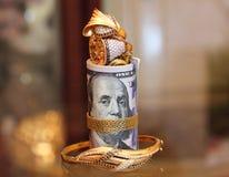 美金与金首饰的卷金钱 库存图片
