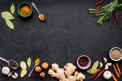 美食术,烹饪 鲜美盘秘密  调味料和香料 罗斯玛丽,姜,在黑背景的辣椒 免版税库存照片