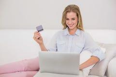 美满偶然白肤金发放松在做网上购物的长沙发 免版税库存图片