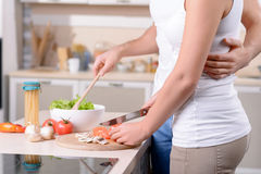 美满的爱恋的夫妇获得乐趣在厨房 免版税库存照片