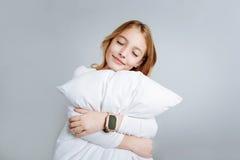 美满的逗人喜爱的女孩拥抱枕头 图库摄影