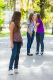 羡慕女孩谈话在她的女朋友后 免版税库存照片